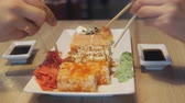 рулон : People eating rolls in japan restaurant or sushi bar.