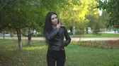 coat : beautiful young girl in black jacket walking in summer park