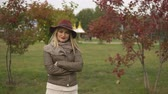 Бургундия : beautiful young woman in hat, scarf and jacket posing in the autumn park Стоковые видеозаписи