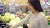 patlıcan : Young woman in the vegetable department of a supermarket chooses eggplant.