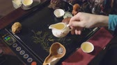 porcelana : Chinese traditions. Master pours green tea into a white cup.