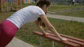 bicepsz : Young sporty girl doing push-ups outdoors.