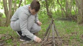 пылающий : young man is lighting a fire in the forest.