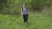 пеший турист : woman with a backpack rises a hill in the forest. Стоковые видеозаписи