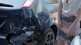 total : frustrated brunette woman is standing near a broken car. Stock Footage