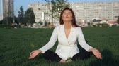 ceo : Beautiful businesswoman in white suit doing yoga for relaxation outdoor, slow motion