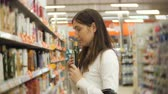 по уходу за телом : Beautiful woman looking at cosmetics in supermarket. Attractive girl buying cosmetic products.