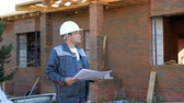 ev idaresi : Adult man wearing white hardhat and looking at paper plans standing outdoors of building under construction Stok Video