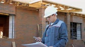 contramestre : Man in white hardhat and overall holding paper plans of building and using phone outside on site