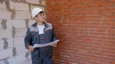 ev idaresi : Adult man in hardhat holding paper draft plan of building standing in empty room of house under construction