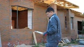 rascunho : Adult man working on site of modern house and standing outdoors with paper draft looking away.