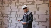 rascunho : Adult man in empty bare room holding paper plans of building under construction and monitoring interior