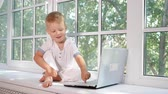 portátil : Cute little boy using laptop at home, slow, motion Stock Footage