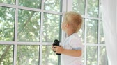 vislumbre : Side view of little boy holding black binocular and looking away in window exploring nature