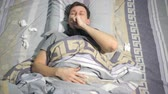 tosse : Ill man with flu and runny nose wipe his nose with a tissue while lying on couch at home, 4k. slow motion Vídeos