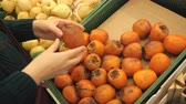 zvětralý : close up of a female hand checks the persimmon, slow motion