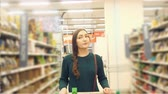grocer : Female customer witht rolley shopping in supermarket. Stock Footage