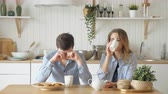sleepy couple drinking coffee at table in kitchen