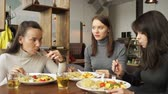 slow motion of three woman friends are eating together in cafe and talking, enjoying their food. Front view. Стоковые видеозаписи