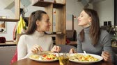 delisious : slow motion of two woman friends are eating together in cafe and talking, enjoying their food. Front view. Stock Footage