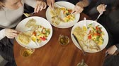 zöldség : Three women friends are eating their food in cafe. Plates on the table top view. Hands close-up.