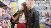 решать : Young couple in supermarket is choosing soft toy for gift, close-up