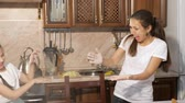 mischief : Portrait of playful mom and her teen daughters throw flour to each other while cooking in the kitchen. Family cooking at home, laughing and smiling people. Stock Footage