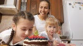budino : Portrat of mom and daughters are sniffing cooked homemade chocolate cream cake with blueberries, raspberries and physalis in kitchen at home. Teen girl is taking berry from the cake and eating it.