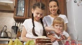 budino : Family cooking at home with children, portrait of mom with two daughters are decorating birthday chocolate cream cake with different berries together in kitchen at home. Filmati Stock