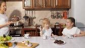 masa örtüsü : Birthday surprise from mom. Mother brings the chocolate homemade cake to her daughters having a tea sitting in kitchen at home. Stok Video