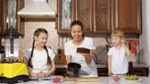 estanho : Young brunette mother is baking birthday cake with her two little daughters in the kitchen, she is pulling the cake sponge out of the cake mold. Family cooking.