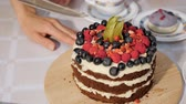 budino : Woman cuts a piece of birthday homemade chocolate cake with cream and sponge cakes layers decorated fresh berries, closeup.