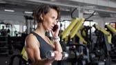 úleva : Portrait of athletic mature woman is making set of reps exercise for biceps with dumbbells in hands in gym. She is speaking mobile phone. Life and sport concept.