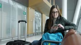 registrar : Young woman traveller passes e-check in mobile phone waiting her flight in airport. She is sitting at hall with her suitcase and backpack.