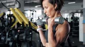halter : Portrait of athletic mature woman is making set of reps exercise for biceps with dumbbells in hands in gym. She is lifting dumbbells. Training and sport concept.