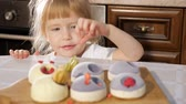 украшать : Portrat of little cute girl is decorating small cake with raspberry in kitchen table at home and she is eating berries.
