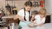 tentar : Girls sisters are mixing ingredients using beater in a bowl in kitchen at home, the younger sister tries all tastes.