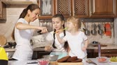 sponge cake : Daughters helps her mom to cook cream for cake, they eats and tastes cream using culinary spatulas while woman pours it in a bowl from blender.