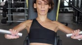 úleva : Portrait of slim woman is doing exercises for arms muscles on training machine. She is sitting and pushing away some reps. Sports workout in the gym, front view Dostupné videozáznamy