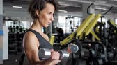 weights : Portrait of athletic mature woman is making set of reps exercise for biceps with dumbbells in hands in gym. She is lifting dumbbells. Training and sport concept.