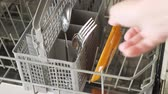 lave vaisselle : Man puts a dirty plates and cutlery in dishwasher. Top view, close up. Vidéos Libres De Droits