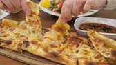 suluguni : Traditional azerbaijani lunch with fresh khachapuri bread filling suluguni cheese and vegetables. Woman is taking a slice of khachapuri from wooden board to eat, hands closeup. Stock Footage