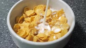 milk pouring : Preparing fast breakfast with cereal. Pouring milk in bowl with dry cornflakes. Traditional morning food. Stock Footage