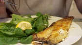 forchetta : Full frying small fish served with piece of lemon, tomato and arugula salad leaves in white plate. Woman is eating fish with fork and knife in restaurant, dish closeup. Filmati Stock