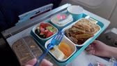 servir : Lunch in plane: bread, meat with vegetables and rice, pieces of cheese, dried apricot, salad and beverage in cup. Woman is eating in airplane during flight food served on tray, hand with fork closeup.