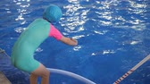 pływak : Little girl on swim lesson in sport school. Child girl learns to dive in pool from a standing position with her hands outstretched, side view. She wears in swimsuit, cap and goggles. Wideo