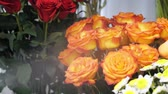 aveludado : Care of plants in floristry studio. Spraying red and orange roses with water from a sprayer in flower shop, closeup view. Moisturizing fresh flowers for long-term storage and sale.