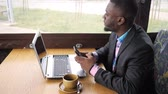 pensamento : Black businessman works on laptop with smartphone in cafe and looks at window, close-up Vídeos