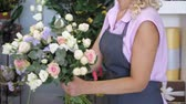 fiore vaso : Professional florist woman creates lovely flower bouquet with roses, leaves and gypsophila. Blonde middle aged woman in uniform works in flower shop. She makes bunch of tender colours pink and yellow.