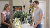 продавщица : Young man customer buys huge beautiful bunch in flower store. Woman florist sellor gives flower bouquet to man customer in modern floristry shop. Work day in floral business.